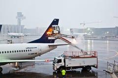 O trabalhador remove o gelo da asa da planície Foto de Stock