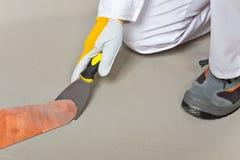 O trabalhador remove o tapete velho do assoalho com o trowel Foto de Stock