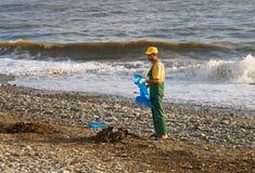 O trabalhador remove os restos na praia pelo mar Fotos de Stock Royalty Free