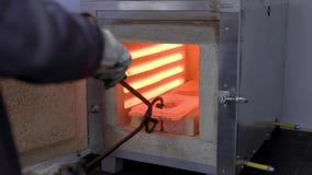 O trabalhador remove a peça de metal encarnado fora da fornalha com tenazes de brasa grandes, planta industrial video estoque