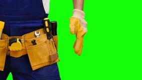 O trabalhador remove uma chave de fenda de sua correia da construção Tela verde Fim acima video estoque