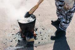 O trabalhador repara o telhado com alcatrão derretido de uma cubeta com uma vassoura Alcatrão do reparo do telhado fotografia de stock