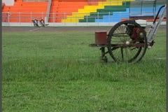 O trabalhador sega o cortador do gramado no estádio video estoque