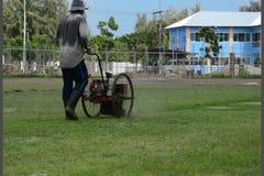 O trabalhador sega o cortador do gramado no estádio filme