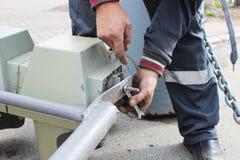 O trabalhador substitui o sinal quebrado com um sinal de trabalho Desaparafusando partes com as lâmpadas da asseguração imagem de stock royalty free
