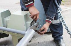 O trabalhador substitui o sinal quebrado com um sinal de trabalho Desaparafusando partes com as lâmpadas da asseguração foto de stock