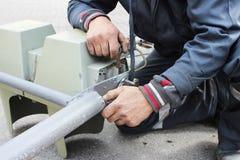 O trabalhador substitui o sinal quebrado com um sinal de trabalho Desaparafusando partes com as lâmpadas da asseguração fotos de stock