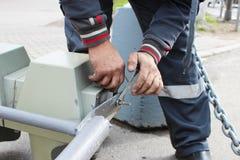 O trabalhador substitui o sinal quebrado com um sinal de trabalho Desaparafusando partes com as lâmpadas da asseguração fotografia de stock