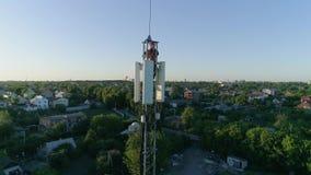 O trabalhador técnico na mostra celular superior da antena manuseia acima, tiro aéreo da torre da telecomunicação filme