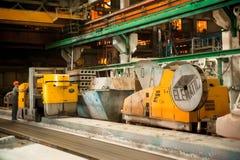 O trabalhador trabalha na máquina na produção de placas Fotografia de Stock