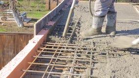 O trabalhador tratou o vibrador concreto líquido em um molde com os encaixes filme