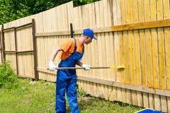 O trabalhador usa o rolo de pintura para aplicar a pintura amarela na placa de madeira Fotografia de Stock