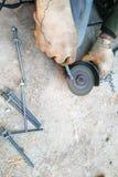 O trabalhador usa um moedor de ângulo para apontar os parafusos, um plano do close-up fotos de stock