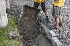O trabalhador usou o carrinho de mão transportando a areia e as pedras para a construção da estrada do passeio Ferramentas da con imagens de stock