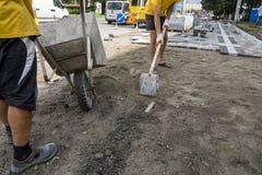 O trabalhador usou o carrinho de mão transportando a areia a um outro homem com uma pá para a construção da estrada do passeio imagens de stock royalty free