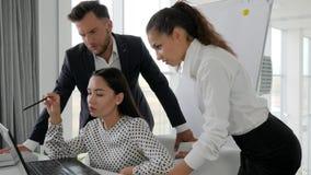 O trabalho coletivo, gerentes aproxima a tela do portátil que falam um com o otro, trabalhadores criativos video estoque
