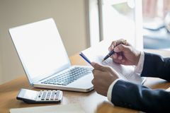 O trabalho do homem de negócio em estatísticas e em gráficos de negócio, homem de negócios que guarda uma pena está trabalhando c fotos de stock