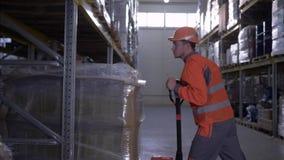 O trabalho duro, trabalhador do armazém retira um caminhão pesado a cremalheira vídeos de arquivo