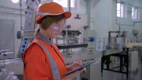 O trabalho fêmea pesado, menina do especialista da fábrica no capacete de segurança usa a tabuleta do computador para o hardware  filme