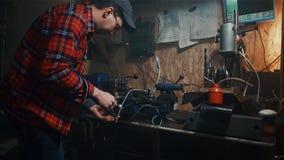 O trabalho mestre masculino na máquina velha do torno que processa o voo do metal acende em uma garagem escura da oficina filme