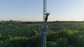 O trabalho perigoso, o técnico de rádio no capacete de segurança obtém para baixo da torre da telecomunicação com ajuda de amarra vídeos de arquivo