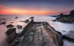 O trajeto da rocha ao oceano, em relação a um por do sol colorido fotos de stock