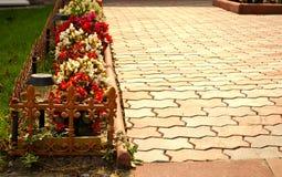 O trajeto de pedra no jardim flanqueou com flores coloridas, fundo da queda Foto de Stock
