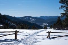 O trajeto nevado corta completamente a cerca na frente da cordilheira imagem de stock royalty free