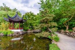 O trajeto perto de uma lagoa com uma ponte de madeira e um pavilhão refletiu i imagens de stock royalty free