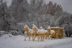 O transporte dourado aproveitou por quatro cavalos, cobertos com a neve fotografia de stock royalty free
