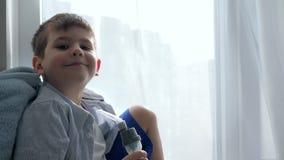 O tratamento da asma, criança respira através do inalador no close-up do hospital filme