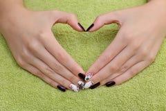 O tratamento da beleza das unhas, mãos mostra o sinal do coração Fotos de Stock Royalty Free