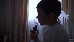 O tratamento da criança, rapaz pequeno doente trata a inflamação das vias aéreas através do nebulizer com a medicamentação vídeos de arquivo