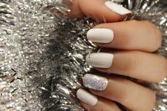 O tratamento de mãos de ano novo, cor do prego do Natal, pregos brancos da cor foto de stock