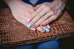 O tratamento de mãos das mulheres em um fundo das peles do crocodilo Foto de Stock