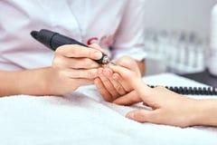 O tratamento de mãos das mulheres, tratamento de mãos mecânico, cuidado da mão Foto de Stock
