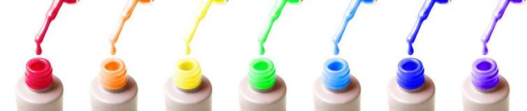 O tratamento de mãos largo extra do arco-íris engarrafa o verniz para as unhas, as escovas e as gotas do gel de cores vermelhas,  fotografia de stock