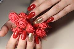 O tratamento de mãos prega o vermelho e o ouro imagens de stock