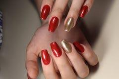 O tratamento de mãos prega o vermelho e o ouro foto de stock