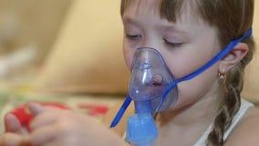 O tratamento de vapor da inalação do ingaliruut da menina, criança doente no hospital joga no telefone filme