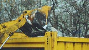 O trator com uma grande cubeta carrega a neve vídeos de arquivo