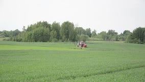 O trator de exploração agrícola monta a colheita nova para fertilizar os campos das pragas vídeos de arquivo