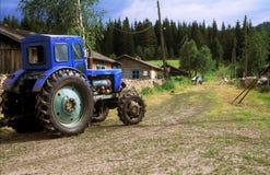 O trator de exploração agrícola na rua da vila Imagem de Stock Royalty Free