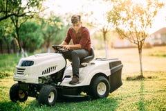 o trator do lawnmower com o trabalhador que faz ajardinar funciona no por do sol do fim de semana Fotografia de Stock Royalty Free