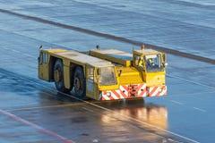 O trator do reboque do aeródromo está conduzindo ao longo dos trajetos da direção no aeroporto imagem de stock