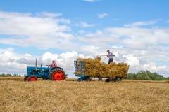 O trator e o reboque azuis do fordson do vintage velho na colheita colocam Imagens de Stock Royalty Free