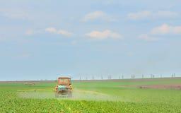 O trator fertiliza colheitas no campo imagens de stock