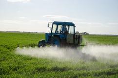 O trator fertiliza o inseticida e o inseticida do campo Foto de Stock Royalty Free