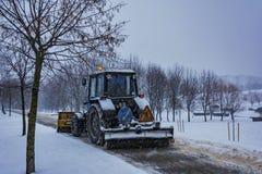 O trator limpa a neve do passeio durante a queda de neve Imagem de Stock