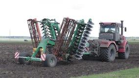 O trator monta no campo com o sistema de plantar feijões filme